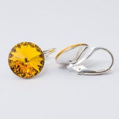 Swarovski Rivoli Earrings 12mm Sunflower  Dimensions: length: 1,7cm stone size: 12mm Weight ~ 3,18g ( 1 pair ) Metal : silver plated brass Stones: Swarovski Elements 1122 12mm Colour: Sunflower 1 package = 1 pair Price 16,90 PLN(about 4 EUR)