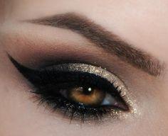 Black and glittery pale gold eye makeup plus black winged eyeliner