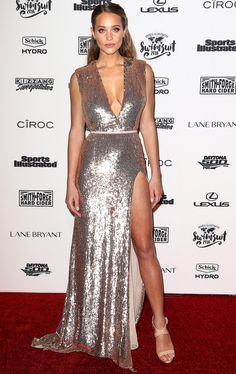 HANNAH DAVIS in a shimmering, low-cut, high-slit gown and strappy nude Giuseppe Zanotti sandals