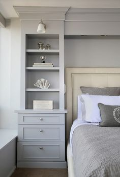 Gorgeous bedroom boasts gray built-in bookcase with lower drawers accented with round brushed nickel pulls lit by a frosted glass wall sconce beside an ivory leather bed with nail-head trim layered with gray bordered bed linens and a gray matelasse coverlet with matching shams.