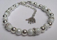 Armband van witte snow glas parels, strass tussenstukjes en metallook kralen.