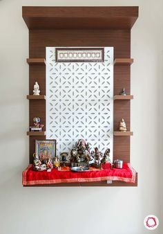 A wall mounted pooja unit with one drawer and shelves