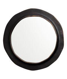 Rund spegel med ram i antikbehandlad metall.