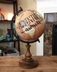"Old globe with vinyl letters. ""Adventure Awaits"" or ""Be the change you wish to see in the world"""