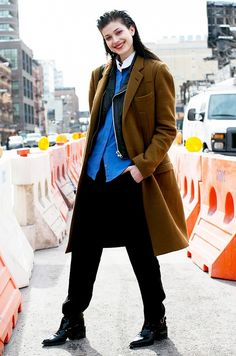 Black trousers are livened up with a camel coat, leather jacket, and blue button-down.