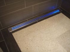 This shower drain has its own LED battery pack, which activates when the shower turns on. When water enters the drain, the LED light comes on. The designer incorporated the light so the clients would have more illumination and a way to orient themselves in the shower.