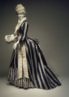 1885 walking dress from the House of Worth. As the name implies, it is an outdoor garment worn for walks. It therefore reflects seasonal change to a great degree, incorporating warm overgarments such as coats, capes, hats and muffs into its very design.