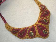 Detalle collar babero realizado en fieltros ocre y bordo con aplicaciones mostacillas bronce y pepas dorado viejo