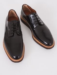 Impeccably made and extremely comfortable, Common Projects is known for it's classic styles. These black lace-up oxfords with a rounded toe in glossed black leather feature a brown contrast leather li