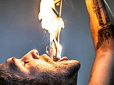 A man holding a stick which is on fire, in his mouth