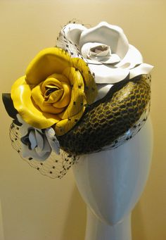 Crown of roses. Statement leather at its best. A black leather base has been blocked and then covered in a fine yellow crin lace. Massive leather handmade roses are all stitched by had and sewn in place to create a tumbling crown effect. Finished with black leather leaves and a sweep of vintage black French veiling