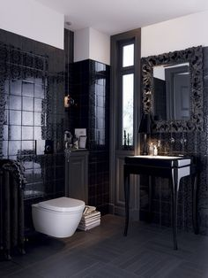 The sleek, detailed, black tile walls make for a powder room that is glamorous and luxurious, yet modern.