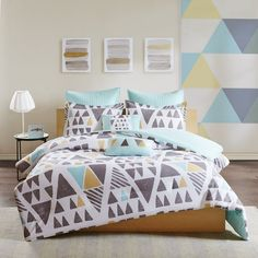 Shape up your bedroom's look with the 7 Piece Duvet Cover Set. Showcasing matching geometric patterns on a bright white backdrop, the two shams and chic duvet cover deliver comfort in style. Extra dimension and charm are added to the design with the varying sized and colored triangles. The solid aqua reverse complements the playful pattern while providing a pop of color. Two quilted Euro shams add texture and charm to the bedding set. The two decorative pillows included in this duvet cover…