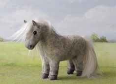 Flecked grey Falabella with long mane and tail.