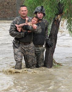Sgt. Robert Huff and  Cpl. Patrick O'Rourke with a Military Police Platoon rescue an Afghan child from encroaching flood waters in the Nari Shahi village in the Beshood District of eastern Afghanistan's Nangarhar province on July 28. The flooding was caused when more than 6 inches of rain enveloped the area in a few hours. The platoon was returning from a patrol in the district and stopped to help the villagers when they realized the dangers of the situation.
