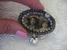 My husband brought me home a bunch of vintage tiny tin tart pans or tiny patty pans. I repurposed one of the pans into a shabby prim little brooch with a real postcard photo of two sweet little girls. I surrounded the photo with vintage rhinestones, one larger rhinestone and added a silvertone puffy heart dangle. The patty pan is 2 across. A pinback has been soldered to the back with jewelry grade, non-leaded solder. This little brooch is such a little nugget of unique upcycled goodness…