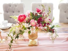 Lush pink ranunculus centerpiece on a pink chiffon table runner