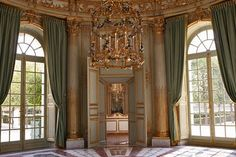 Le Petit Trianon, The main salon is octagonal with an inlaid marble floor and is surrounded by four cabinets in a cruciform arrangement. The walls are gilded with cherubs highlighting each entrance. Cherubs & birds are also featured on the circular cornice which is supported by eight Corinthian columns. Four arched French doors provide light, exterior views and access
