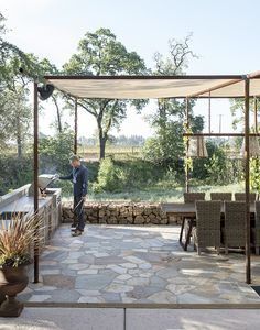 An outdoor dining area is shaded by a mesh canopy suspended by old drilling pipes.