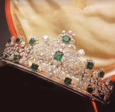 a gorgeous Cartier belle epqoue diamond an emerald tiara with approx four diamond foliate and square-cut emeralds either side of the central foliate scroll motif, with square-cut and emerald-ctu emeralds with in it; all rising from a base of diamonds and emeralds