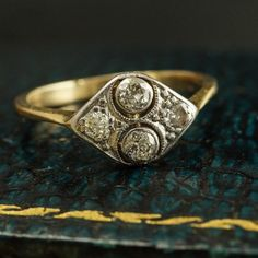 This unusual two-tone Deco ring is modeled in the shape of an eye. The platinum face sparkles with two .09ct transitional cut diamonds bezel-set within cutaway halos. The north-south oriented primary stones are flanked by two .03ct single cut diamonds in flush bead settings. The 18k yellow gold mounting features tapered knife edge shoulders and a half round hoop.   Materials: 18k yellow gold, platinum. 2 x .09ct transitional cut diamonds, 2 x .03ct single cut diamonds  Age: c. 1925…