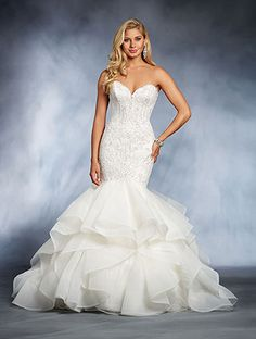 A princess wedding gown with a strapless, sweetheart neckline, dropped waistline, and flared ruffle skirt.