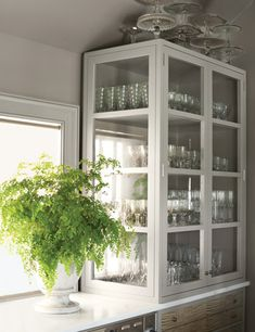 """In Martha's """"servery"""" off the kitchen, used for washing and storing dinnerware, she wanted storage that felt like furniture, not cabinetry. """"This apothecary-like glass case, one of a pair, provides the solution,"""" she says. Light shines through it, opening up the small room and glinting off the glasses and dishes inside."""