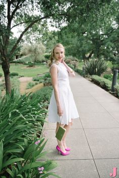 Dress up a simple white shirt dress with a pair of pink heels and some gold accessories. It's perfect for a summer date night.