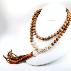 """Leather Tassel Necklace of Wood and Shell Knotted on Silk TO BUY: Comment with your email address and you'll receive a secure checkout link. Price: $91.00 This necklace is a wonderful summer accessory great for layering or wearing on it's own. The focus of this necklace is the 4"""" deer hide leather tassel with burnt orange silk wrap accent that hangs from a sterling silver circle. Flanking the tassel are beautiful shell beads and warm honey colored wood beads hand knotted on 100% silk thread…"""