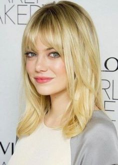 Emma Stone: Medium Length straight hair with bangs and layers...