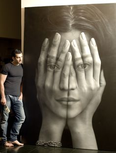 Artist Tigran Tsitoghdzyan created this larger than life painting, titled Mirror. It shows a woman unsuccessfully hiding behind a pair of hands. The surreal piece is meant to reflect todays Internet culture, where its becomes exceedingly difficult to reach any level of anonymity.