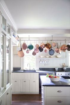 Vintage touches, such as wainscoting and hanging copper pots and pans, respect the old-school authenticity of the kitchen's architecture, despite its 21st-century gadgets | domino.com