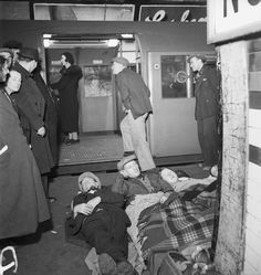 Civilians sheltering in Elephant and Castle Underground Station whilst passengers continue to use the trains, November 1940.