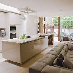 Open-plan kitchen with neutral gloss island unit, granite worktop, wood flooring and brown leather sofa