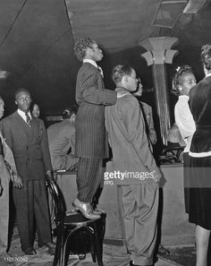 A short man wearing a zoot suit stands on a chair to get a better view of the dance floor at the Savoy Ballroom in Harlem New York in the 1940's