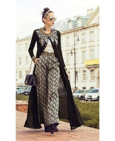 If you're looking for sophistication and elegance, and black is your favourite colour, this sheer long black heavily embroidered jacket-style top is just a perfect choice.  The outfit from Indiwear comes with a parallel palazzo style pant with jaunty decorative details giving you a nice long and shapely silhouette.  Make a super style statement this season in this partywear that they'll be talking about for years to come when you match this dress with black ankle boots and hoop earrings…