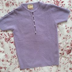 """Vintage Wool-Angora Blend Sweater Gorgeous short sleeve lavender sweater with adorable faux pearl buttons henley-style and on tops of sleeves. In very good vintage condition, no stains, limited pilling, 1 small hole near left shoulder and some runs on bottom right (see pics). Barely noticeable. This has been well cared for! Super soft 50% lambswool, 40% angora, 10% nylon. Label: Tarni. No size tag, measures flat 16.5"""" shoulders, 19"""" bust, 26"""" length. Thanks for looking! Vintage Sweaters Crew…"""
