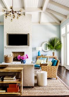 Exposed, painted white, ceiling beams in living room with wall-mounted TV, Sputnik light fixture, wicker furniture, indoor plant in corner with console table and round mirror, and bright pink flowers on coffee table