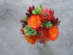 Bridesmaid bouquet of bells of ireland, circus roses, pincushion protea, leucadendron, and red hypericum berries Designed By: hillside-consultants.com