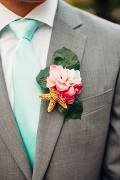 This groom really knows how to dress for a wedding in the sand. The boutonniere's bright floral and starfish accents combined with his aqua tie and gray suit create a summery vibe that falls nothing short of amazing.
