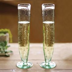Serve Bellinis or your favorite sparkling beverage in these slender Recycled Glass Champagne Flutes. Made of 100% recycled glass, each piece has a unique, extra tall silhouette that works well with rustic weddings and gatherings featuring modern yet charming table decor.