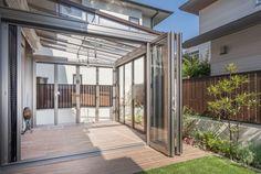 新築に引越ししてから新生活が忙しく、お庭の手入れはなかなか・・・というお悩みは尽きません。共働きのためお庭を愛でることも手入れすることも出来ない施主様のために、ナチュラルテイストなガーデンルームと木目調のタイルデッキをデザイン。 Glass Room, Pergola With Roof, Green Garden, Studio Apartment, Sunroom, Shutters, Canopy, Balcony, Terrace