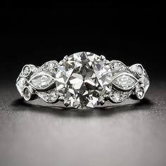 This highly distinctive original Art Deco sparkler, circa 1920s-30s, is artfully hand-fabricated in platinum and features a European-cut diamond weighing 1.88 carat accompanied by a GIA lab report stating L color and SI2 clarity. The scintillating stone sparkles between stylized shoulders set with a pair of marquise diamonds surrounded by curving scrolls set with tiny twinkling single-cut diamonds. An original Jazz Age beauty, currently ring size 6 1/2.