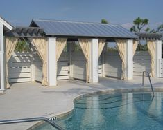 Sunbrella outdoor curtains provide style and privacy around the pool deck.