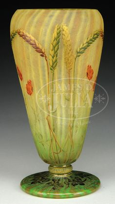 "DAUM NANCY CAMEO AND ENAMEL WHEAT VASE. Exceptional Daum vase has cameo and enameled green, brown and gold wheat motif against an internally decorated acid-textured background of green shading to vertical yellow and orange striping. Vase is further decorated with cameo and enameled red poppies with enameled green stems with gilded highlights. Foot of vase is decorated with cameo and enameled floral design with gilded highlights. Signed on the underside in gilt ""Daum Nancy"" with Cros..."