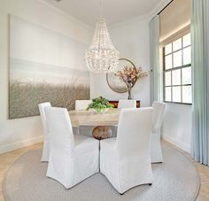 Simple white coastal inspired space - love the different elements - chandelier, table texture, slipcovered chairs, blinds and curtain combination, print - everything !