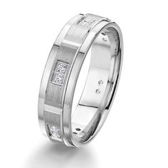 14kt white gold, diamond, comfort fit wedding band. There are 12 round brilliant cut diamonds set in the ring. The diamonds are about 0.12 ct tw, VS1-2 in clarity and G-H in color. The center of the ring has a brushed finish with the edges being polished. Other finishes may be selected or specified. The ring is 6.0 mm wide.