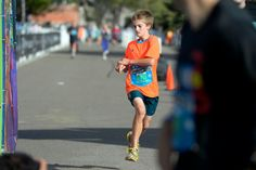 Description of . Ben Rees 14 years old crosses the finish line of the 1/2 marathon with a time of 1:34:30 during the 9th annual Colfax Marathon May 18, 2014. The 26.2 mile Marathon runs through Denver's iconic landmark Mile High Stadium (twice), Sloan's Lake, City Park, Colfax Avenue through Lakewood and Aurora. The Marathon started and finished in City Park where runners enjoyed the rest of the day listening to music by Chris Daniels and the Kings. (Photo by John Leyba/The Denver Post)