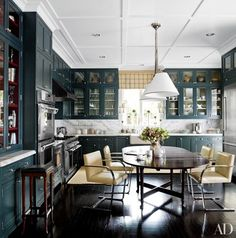 Knoll's Brno chairs surround an antique table in the refreshed kitchen. Powers paneled the ceiling and installed cabinets whose rich gray-green hue gives the space a sense of intimacy. Neolithic Chinese pottery is displayed at the top of the upper cabinets, and the hood, ovens, and range are by Thermador | archdigest.com