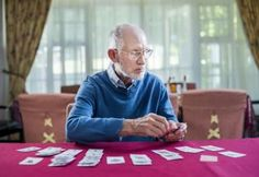 Senior man playing cards in nursing home - Portra Images/Taxi/Getty Images